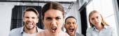 Wütende Geschäftsfrau blickt in die Kamera neben multiethnischen Kollegen auf verschwommenem Hintergrund im Büro, Banner