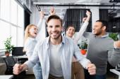 Mosolygó üzletember mutat igen gesztus közel vidám többnemzetiségű kollégák homályos háttér irodai