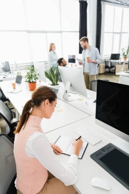 Businesswoman writing on notebook near computer and colleagues on blurred background in office stock vector