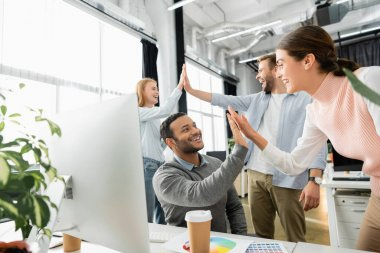 Cheerful multicultural businesspeople giving high five near computer and colorful swatches on blurred foreground in office stock vector