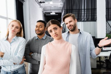 Skeptical multiethnic businesspeople looking at camera in office stock vector