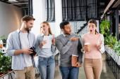 Multikulturelle Geschäftsleute mit digitalem Tablet und Kaffee zum Reden im Büro