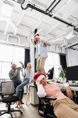 Businesswoman sleeping in santa hat near cheerful multiethnic colleagues with champagne on blurred background