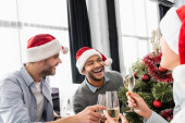 Multiethnic businesspeople toasting with champagne near christmas tree in office