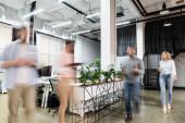 Rozmazání pohybů podnikatelů procházejících se v blízkosti počítačů a továren v kanceláři