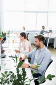 Podnikatel pomocí grafického tabletu a počítače v blízkosti kolegů na rozmazaném pozadí v kanceláři