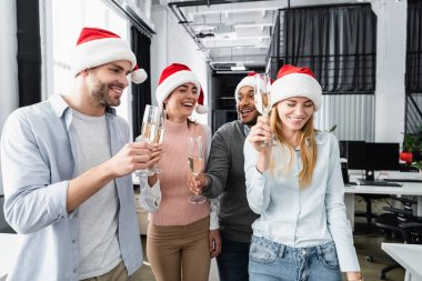 Positive multiethnic businesspeople in santa hats holding glasses of champagne in office stock vector