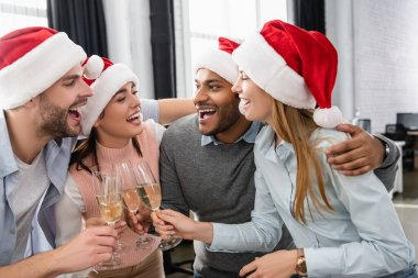 Multiethnic businesspeople in santa hats embracing while clinking with champagne in office stock vector
