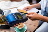 cropped view of woman holding credit card near waiter with payment terminal