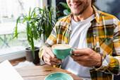 Teilansicht eines lächelnden Mannes, der im Café sitzt und eine Tasse Kaffee mit Latte Art in der Hand hält