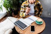oříznutý pohled na volné noze v kavárně v blízkosti notebooku, notebooku, šálku kávy a smartphonu s prázdnou obrazovkou