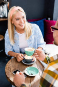 young smiling woman and man on blurred foreground drinking coffee in cafe