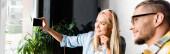 veselé blondýny žena s selfie na mobilním telefonu s přítelem na rozmazané popředí, banner