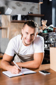 happy barista looking at camera while writing in notebook near smartphone with blank screen on bar counter