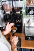 partial view of barista holding portafilter near coffee grinder with grains