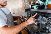 Ausgeschnittene Ansicht des Barista, der den Knopf an der Kaffeemaschine drückt, während er den Filter hält