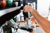 cropped view of barista holding metallic milk mug near steamer of coffee machine