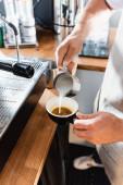 oříznutý pohled baristy, jak nalévá mléko z kovového hrnku do šálku s kávou