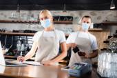 mladí baristé v lékařských maskách při pohledu do kamery v blízkosti platebního terminálu na rozmazaném popředí