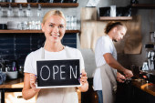 young smiling waiter holding board with open lettering near barista working on blurred background