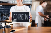cropped view of smiling waiter holding board with open lettering near barista working on blurred background