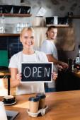 szőke, mosolygós barista holding board nyitott betűkkel közeli kolléga elmosódott háttér