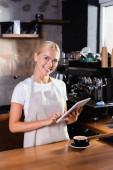 usmívající se blondýnka barista pomocí digitálního tabletu u šálku kávy na baru