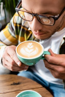 Close up view of man in eyeglasses holding cup of coffee with latte art stock vector