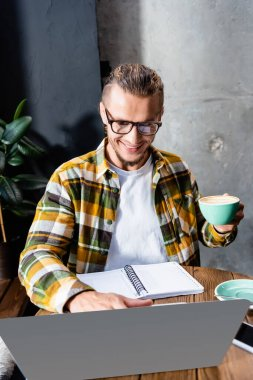 Cheerful freelancer in plaid shirt and eyeglasses holding coffee cup and using laptop in cafe stock vector