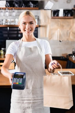 Cheerful blonde barista holding payment terminal and paper bag, blurred foreground stock vector