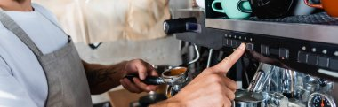 cropped view of barista operating coffee machine while holding portafilter, banner