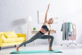 Blondýnka sportovkyně stojící v józe asana na fitness podložce