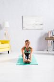 Lächelnde Sportlerin dehnt sich bei Yoga-Übungen auf Fitnessmatte