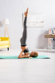 Side view of barefoot sportswoman with raised legs practicing yoga on fitness mat
