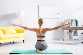 Back view of woman practicing yoga on fitness mat on floor at home