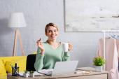 Veselý na volné noze drží pohár a pero při práci s papíry a notebook na rozmazané popředí doma