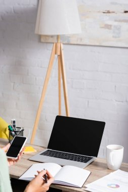 Laptop with blank screen near papers and cup on table near freelancer holding smartphone and pen on blurred foreground stock vector