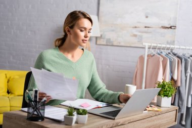 Blonde freelancer holding documents while using laptop near cup and plants on blurred foreground stock vector