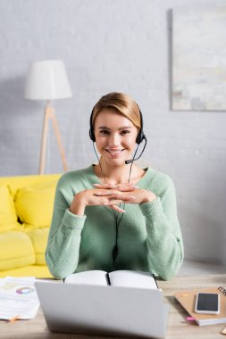 Smiling freelancer in headset looking at camera near notebooks, papers and devices on blurred foreground at home stock vector