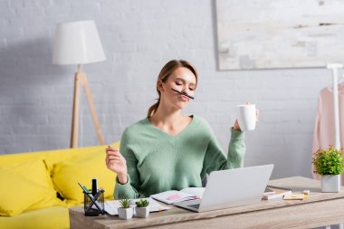 Freelancer holding cup and pen near lips while working with papers and laptop at home stock vector