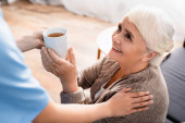 usmívající se starší žena s šálkem čaje od zdravotní sestry na rozmazané popředí