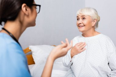 Positive elderly woman touching chest while talking to nurse gesturing on blurred foreground stock vector