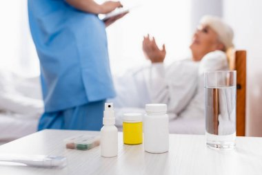 Table with pills containers, throat spray and glass of water near nurse and patient on blurred foreground stock vector