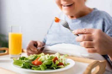 Cropped view of joyful woman having breakfast in hospital, blurred background stock vector