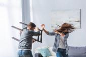 Abusivní muž drží židli blízko křičící manželka doma