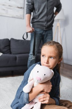 Frightened girl embracing soft toy near father with waist belt on blurred background at home stock vector
