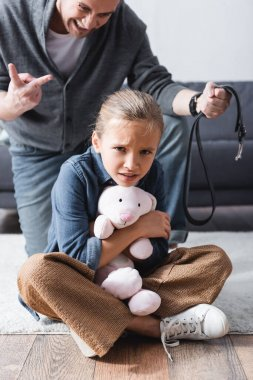 Scared child holding soft toy near angry father with waist belt on blurred background stock vector