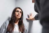 Woman with bruises on face looking at abuser on blurred foreground near walls