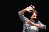 Vyděšená žena s modřinami a lepicí páskou ukazující stop gesto izolované na černé