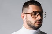 Mladý muž v brýlích a roláku poslouchá hudbu v bezdrátovém sluchátku izolované na šedé